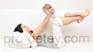 Мама лежа на спине, качает малыша на согнутых ногах, держа за руки