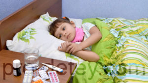 Ребенок лежит на кровати, рядом тумбочка с лекарствами