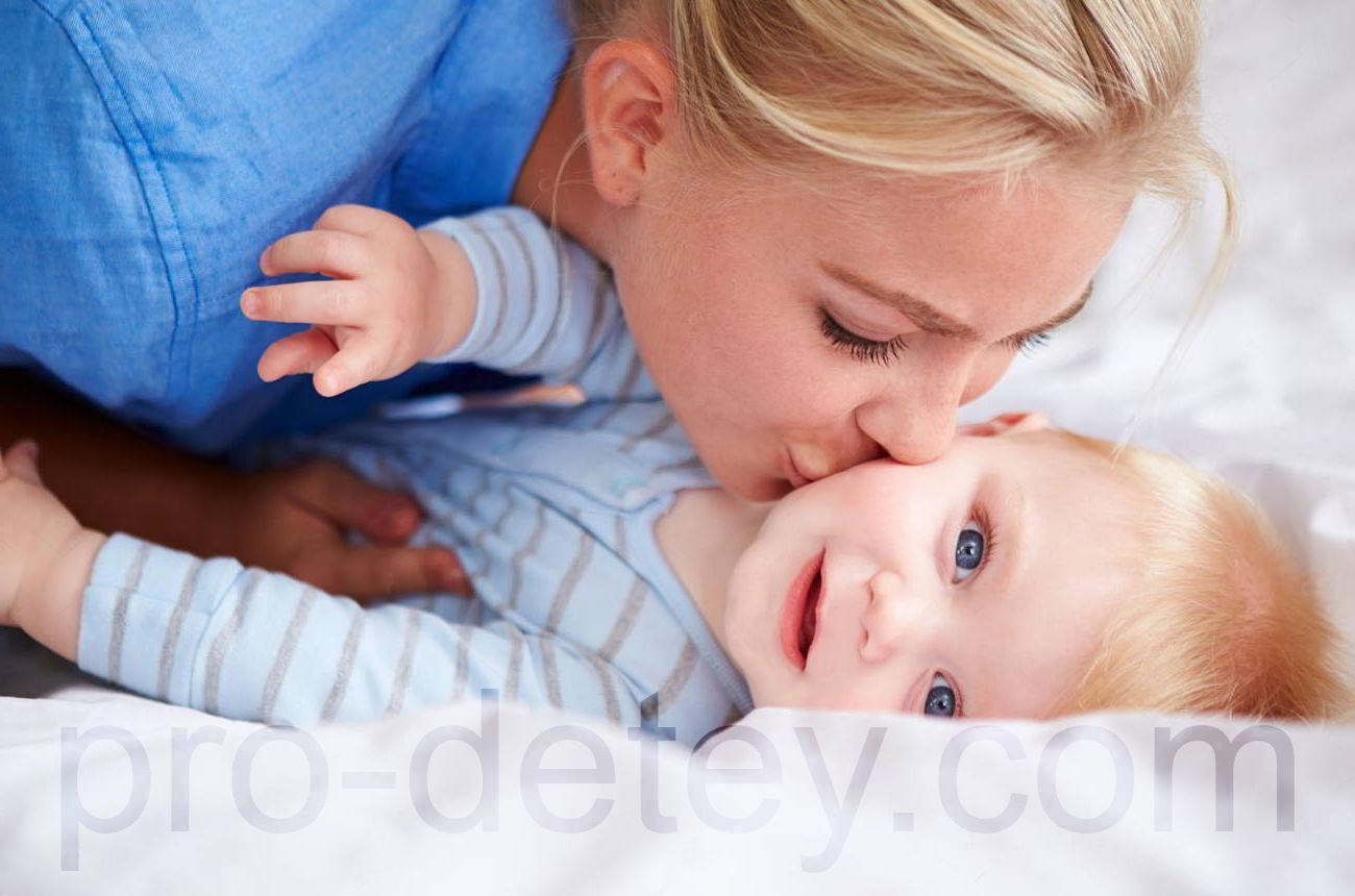 Мама целует лежащего в кровати ребенка, который не спит