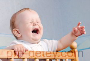 Ребенок стоя в кроватке плачет и просится на руки