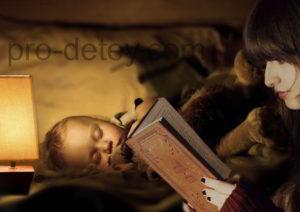 Ребенок в кроватке в обнимку с игрушкой, горит ночник, мама рядом читает книгу